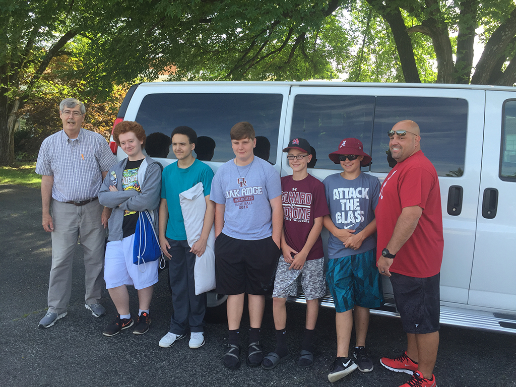 5 teenage boys and two adult males in front of a van